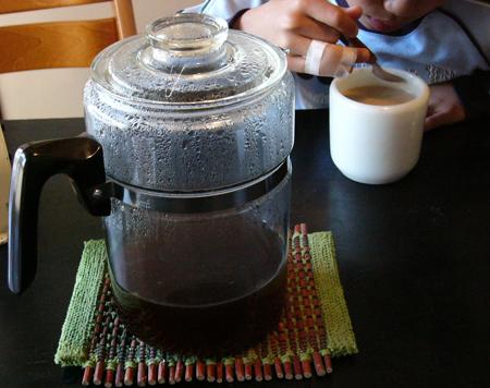 コーニングハンドルレスマグにパイレックスパーコレーターでいれたコーヒーをいれて飲むお兄ちゃん